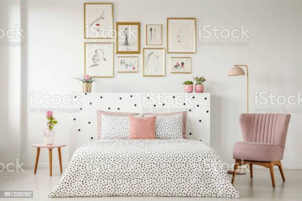 Feminine Bedroom Interior With A Double Bed With Dotted Sheets Armchair Art Collection And Plants - Fotografie stock e altre immagini di Ambientazione interna