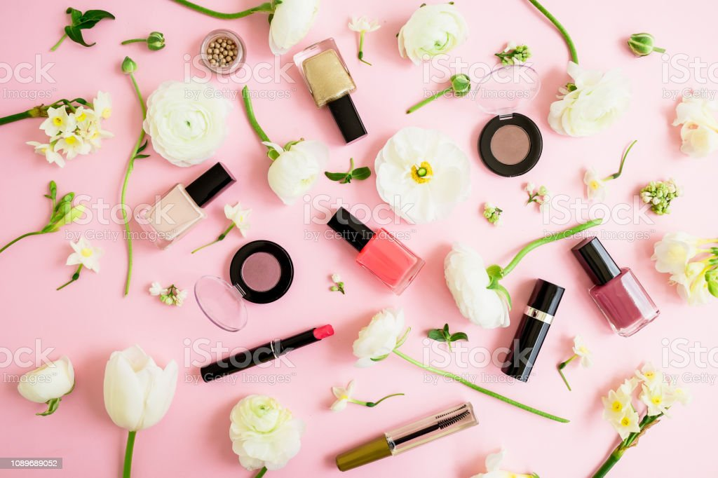 Feminine cosmetics and white flowers on pink background. Flat lay,...