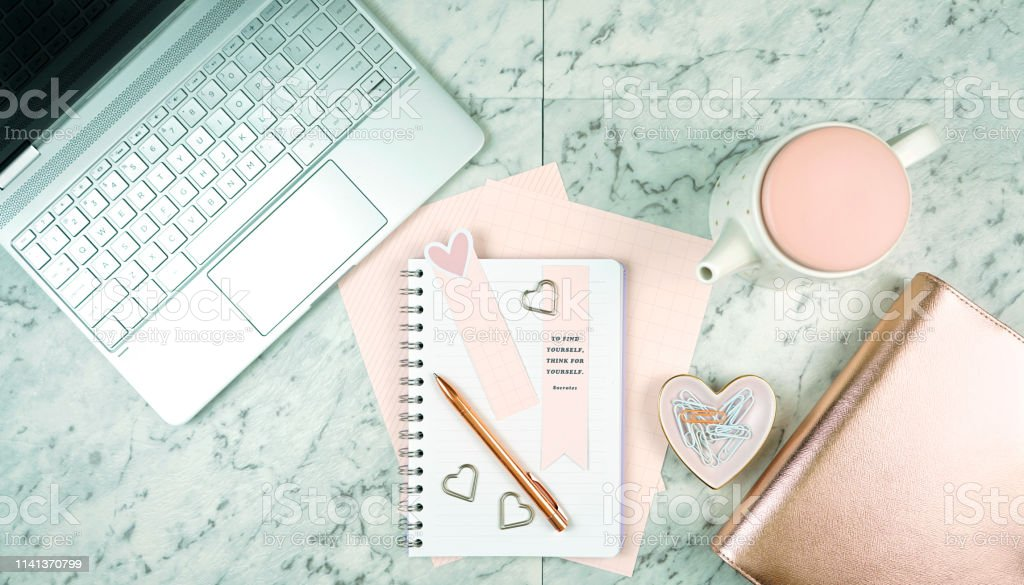 Feminine desk workspace with modern touch screen laptop and pink and...