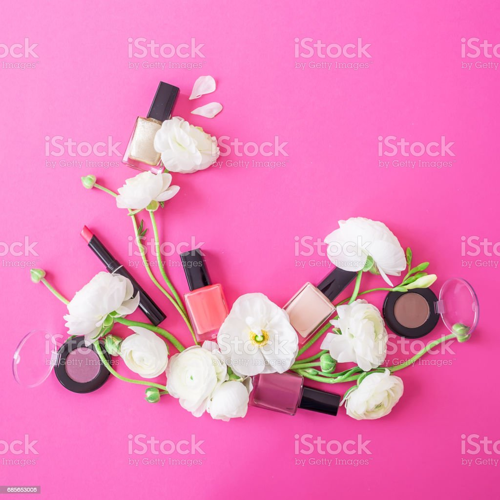 Feminine desk with woman cosmetics and white flowers on pink background. Flat lay, top view. Beauty background royalty-free stock photo