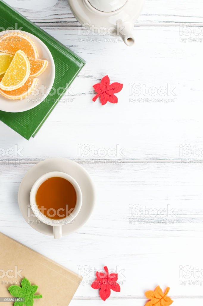 Feminine desk workspace flat lay with diary, eyeglasses, book, tea mug, sweets and felt decor. royalty-free stock photo