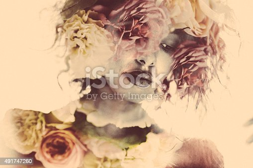 Romantic image of a woman with images of feminine dahlia flowers placed within her form using double exposure effect in soft colours