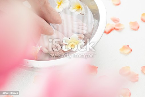Feminine feet and foot spa bowl with flowers