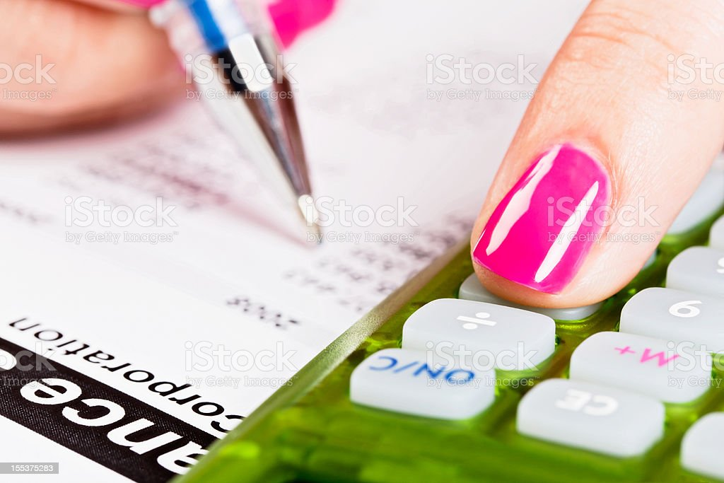 Feminine hand checking corporate balance sheet with pen and calculator royalty-free stock photo