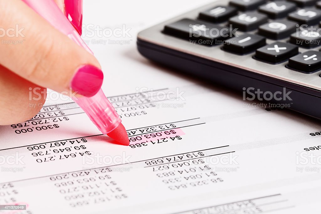 Feminine hand highlights financial document in pink royalty-free stock photo
