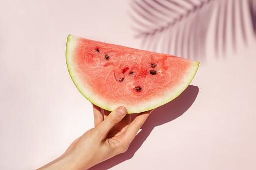Feminine hand holding slice of ripe watermelon