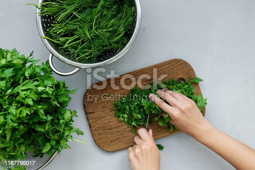 Feminine hands chopping fresh green parsley and dill or fennel on cutting boar on gray wooden table. Top view. Copy space. Harvesting concept