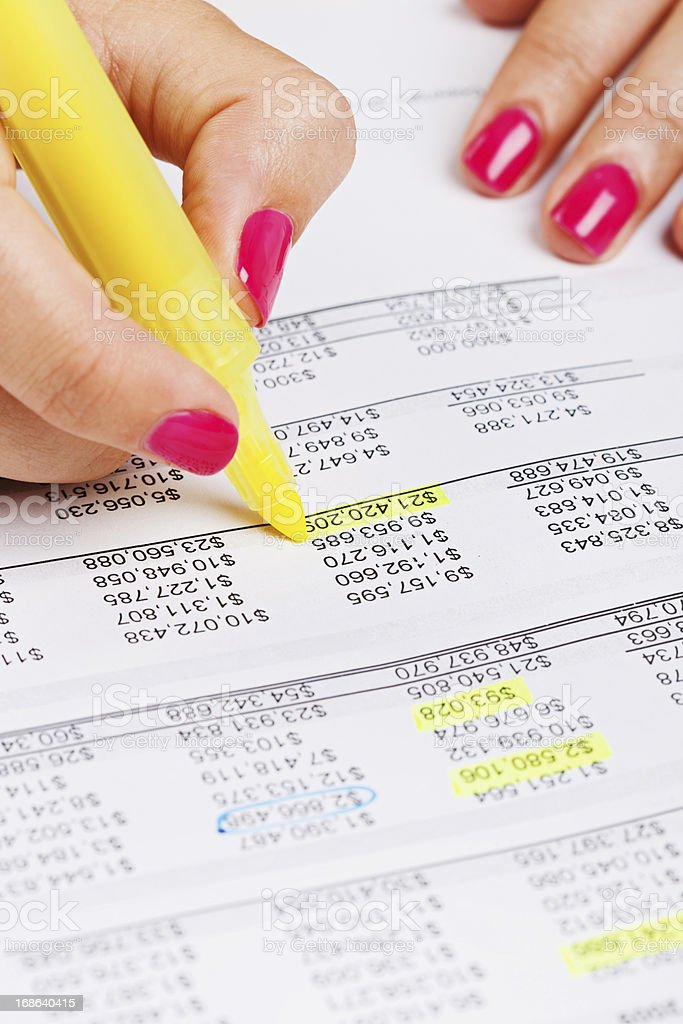 Feminine hands highlight figures on financial document in yellow royalty-free stock photo