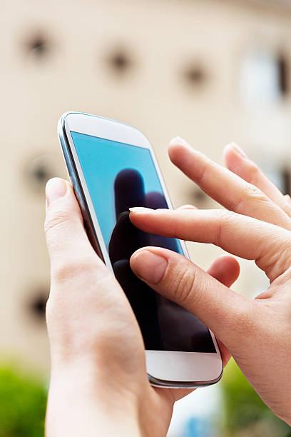 Feminine hands pinching to zoom on smart phone stock photo