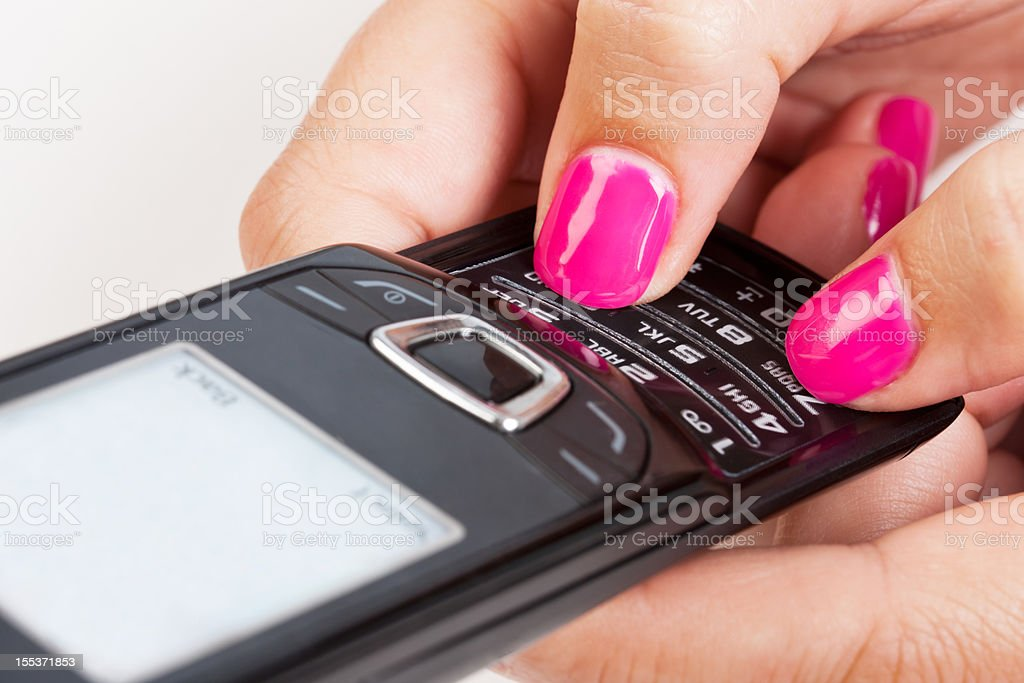 Feminine hands texting on mobile phone in close up royalty-free stock photo