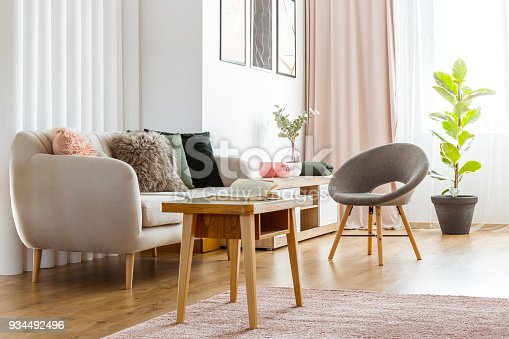 Warm, feminine living room interior with gray armchair, beige sofa and small, woolen coffee table