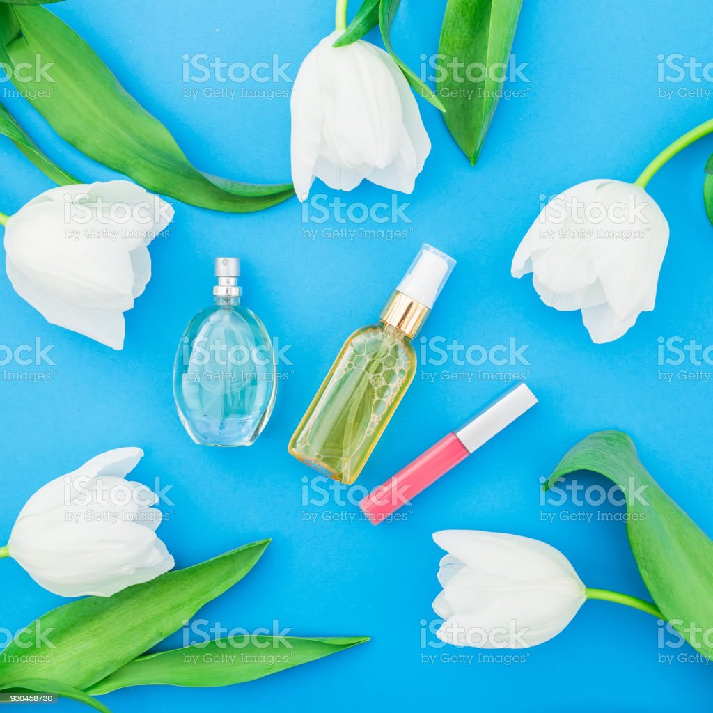 Feminine perfume lipstick and white tulips flowers on blue feminine perfume lipstick and white tulips flowers on blue background beauty blog flat izmirmasajfo