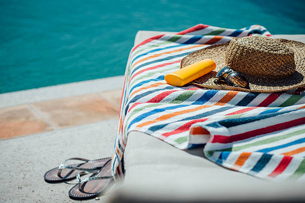 Feminine Pool Necessities Selection of womens items by a pool. There is a colourful towel on the deck chair with a sunhat, sunglasses and sun lotion and some flip flops. poolside stock pictures, royalty-free photos & images