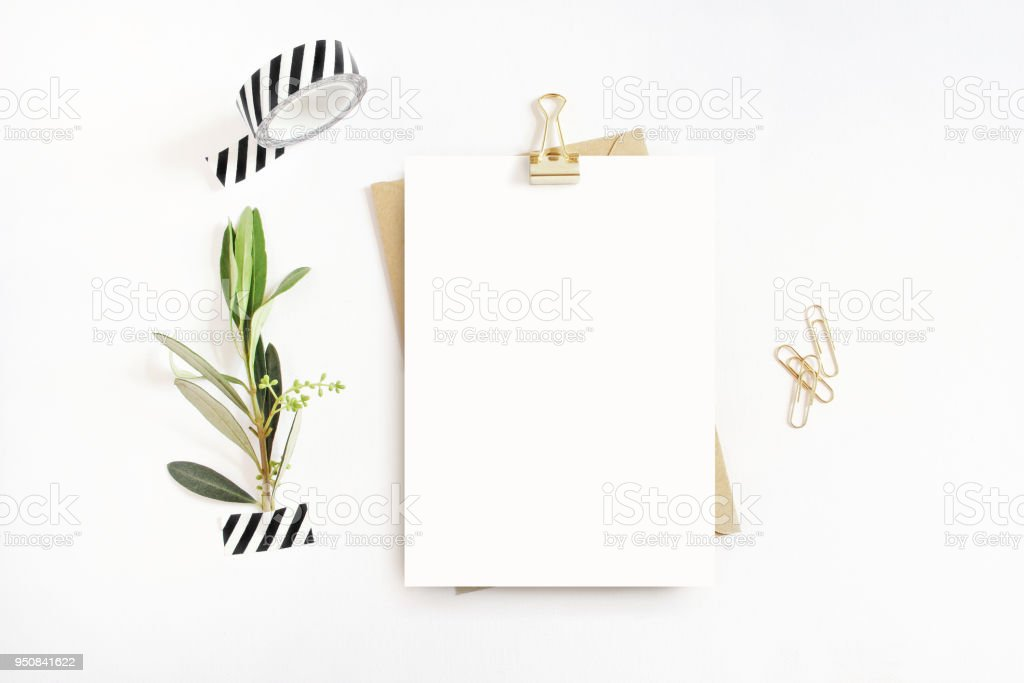 Feminine stationery, desktop mock-up scene. Blank greeting card, craft envelope, washi tape and golden paper, binder clips with olive branch.White table background. Flat lay, top view. stock photo