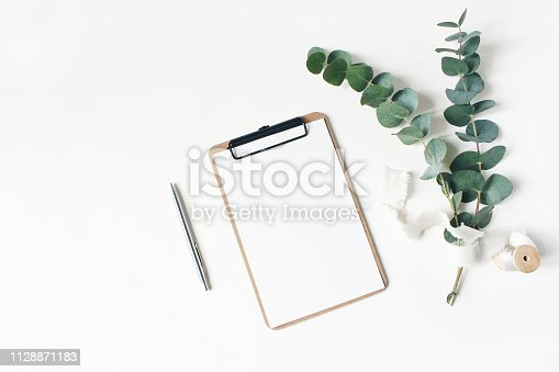 istock Feminine stationery mockup scene. Eucalyptus leaves and branches, silk ribbon, silver pen and blank greeting card in binder clip isolated on white table background. Flat lay, top view. 1128871183