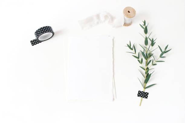 feminine briefpapier, hochzeit desktop-mock-up szene. leere grußkarte, umschlag, schwarze washi tape, seidenband und grünen eukalyptus parvifolia zweig. weiße tabellenhintergrund. flach legen, top aussicht. - bandanzeige stock-fotos und bilder