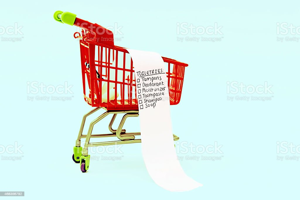 Feminine toiletries shopping list in miniature shopping cart royalty-free stock photo