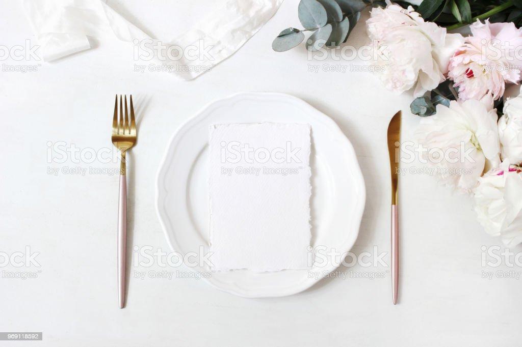 Feminine wedding, birthday desktop mock-up scene. Porcelain plate, blank craft paper greeting cards, silk ribbon, golden cutlery, eucalyptus, peony flowers. White table background. Flat lay, top view stock photo