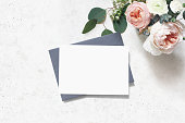 Feminine wedding, birthday mock-up scene. Blank paper greeting card, envelope. Bouquet of eucalyptus leaves, blush pink English roses and ranunculus flowers. Concrete table background, flat lay, top