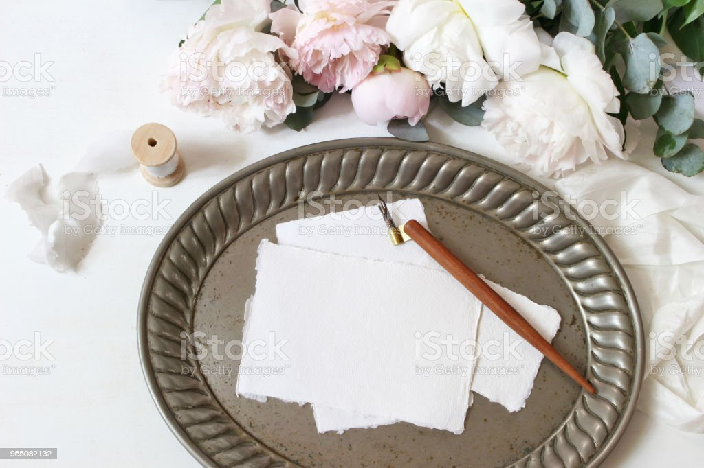 Feminine wedding or birthday table composition with floral bouquet. White and pink peonies flowers, eucalyptus, old vintage silver tray, calligraphy pen and silk ribbons. Blank paper cards, invitations. Flat lay, top view. zbiór zdjęć royalty-free