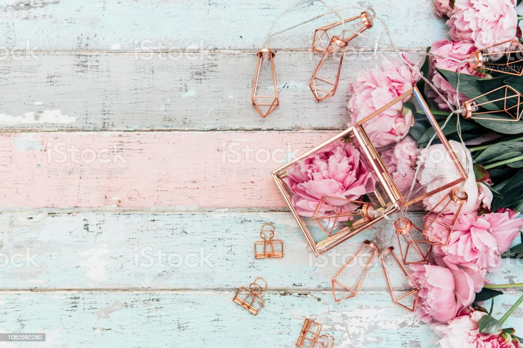 Feminine wedding or birthday table composition with pink peonies and gold decorations on old vintage wooden table.top view, copy space stock photo