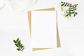 istock Feminine wedding stationery, desktop mock-up scene. Blank greeting card, craft envelope, baby's breath flowers, silk ribbon and lentisk branches. Old white wooden table background. Flat lay, top view. 995684802