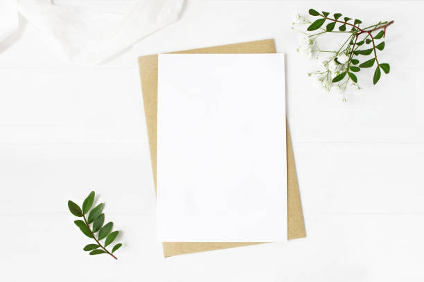 Feminine wedding stationery, desktop mock-up scene. Blank greeting card, craft envelope, baby's breath flowers, silk ribbon and lentisk branches. Old white wooden table background. Flat lay, top view. stock photo
