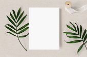 Feminine wedding stationery mock-up scene. Blank greeting card, green palm leaves and silk ribbon on beige textured table background, tropic summer styled photo, web banner. Flat lay, top view.