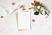 istock Feminine winter wedding, birthday stationery mock-up scene. Blank greeting card, envelope. Dry hydrangea, white roses and gypsophila flowers bouquet. Marble stone table background. Flat lay, top view. 1125431780