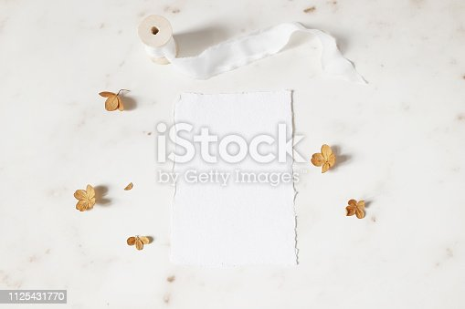 Feminine winter wedding, birthday stationery mock-up scene. Blank deckled edge cotton paper greeting card. Dry hydrangea flower petals, silk ribbon on marble stone table background, flat lay, top view.