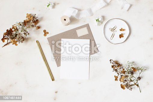 Feminine winter wedding, birthday stationery mock-ups scene. Blank greeting card, kraft envelope, golden pen, dry hydrangea and gypsophila flowers. Marble stone table background, flat lay, top view.