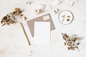 istock Feminine winter wedding, birthday stationery mock-ups scene. Blank greeting card, kraft envelope, golden pen, dry hydrangea and gypsophila flowers. Marble stone table background. Flat lay, top view. 1097461444