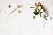 istock Feminine winter wedding, birthday still life scene. Silk ribbon and bouquet of dry maple leaves, hydrangea, white roses and gypsophila flowers. Marble stone table background. Flat lay, top view. 1127395960