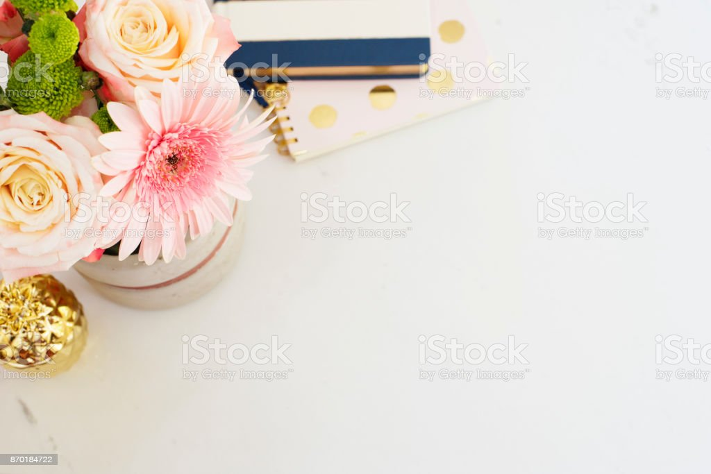 Feminine workplace concept in flat lay style with, flowers, golden pineapple, notebooks on white marble background. Top view, bright, pink and gold