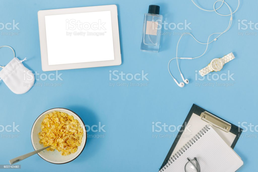 Feminine workspace concept. Frame from tablet, notebook, watches, headphones, plate of corn flakes and perfumes stock photo