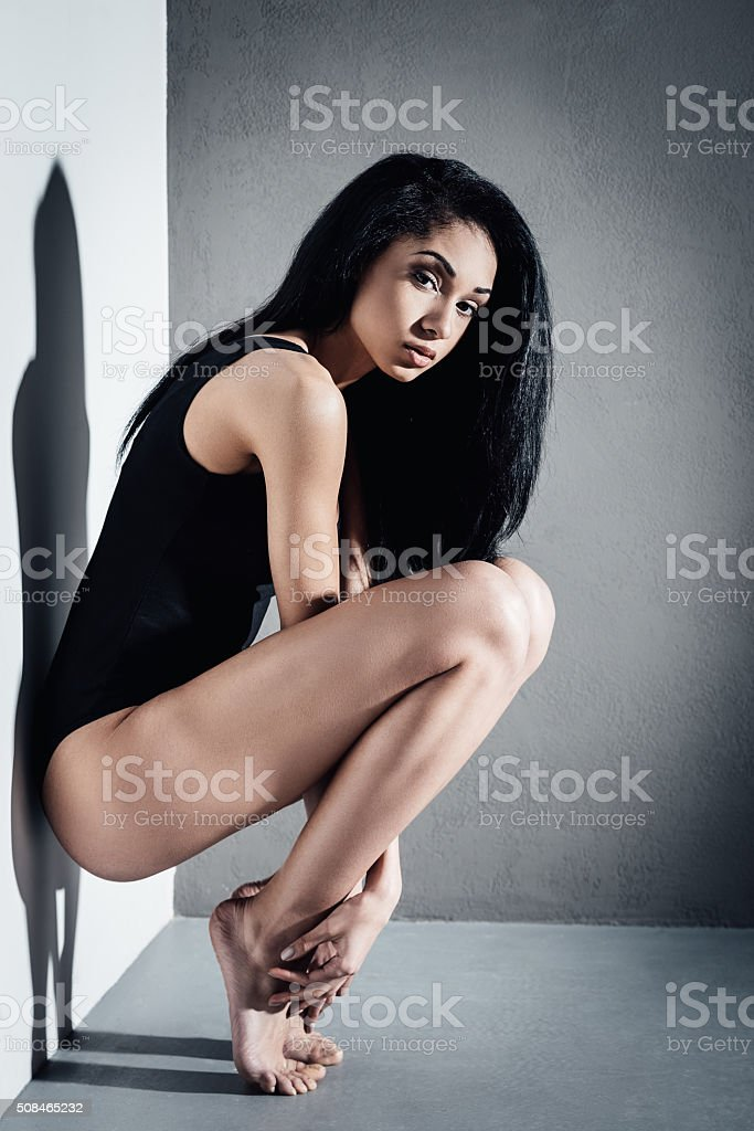 Side view of beautiful young African woman in black swimsuit looking...