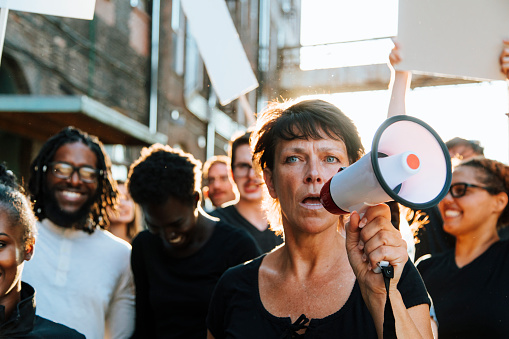 istock Feminist with a megaphone at a protest 1093932478