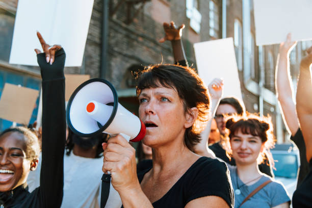 Feminist with a megaphone at a protest Feminist with a megaphone at a protest women's rights stock pictures, royalty-free photos & images