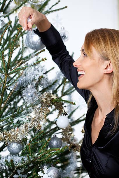 femme qui décore un sapin de Noël femme souriante qui décore un sapin de Noël sapin noel stock pictures, royalty-free photos & images