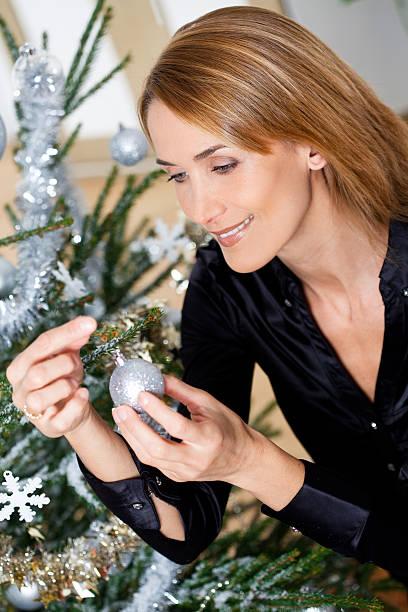 femme qui décore un sapin de Noël femme souriant qui décore un sapin de Noël avec des boules et des guirlandes argentées sapin noel stock pictures, royalty-free photos & images