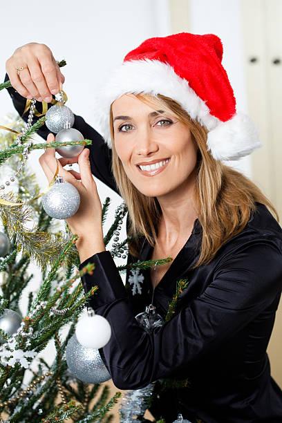 femme qui décore un sapin de Noël femme souriante avec un bonnet de père Noël qui décore un sapin  sapin noel stock pictures, royalty-free photos & images