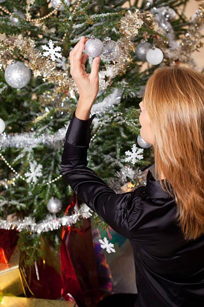 femme qui décore un sapin de Noël femme qui décore un sapin de Noël avec des guirlandes et des boules argentées sapin noel stock pictures, royalty-free photos & images