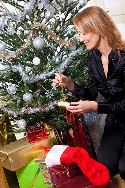 femme qui décore un sapin de Noël femme souriante qui décore un sapin de Noël avec des cadeaux et des guirlandes sapin noel stock pictures, royalty-free photos & images