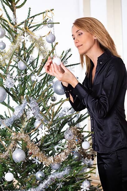 femme qui décore un sapin de Noël femme qui décore un sapin de Noël avec des guirlandes et des boules sapin noel stock pictures, royalty-free photos & images