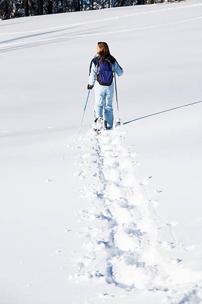 femme qui marche dans la neige avec des raquettes stock photo