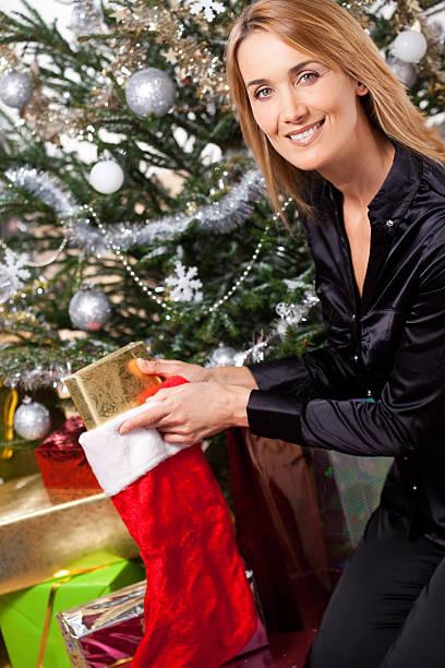 femme qui prépare un sapin de Noël femme souriante qui prépare un sapin de Noël avec des cadeaux sapin noel stock pictures, royalty-free photos & images