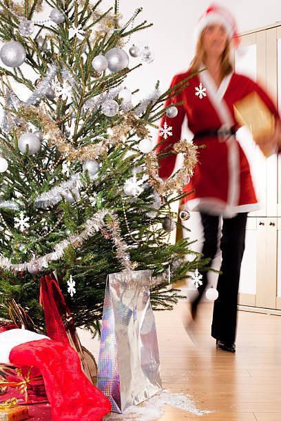 femme qui prépare un sapin déguisée en père Noël femme qui prépare un sapin déguisée en père Noël sapin noel stock pictures, royalty-free photos & images
