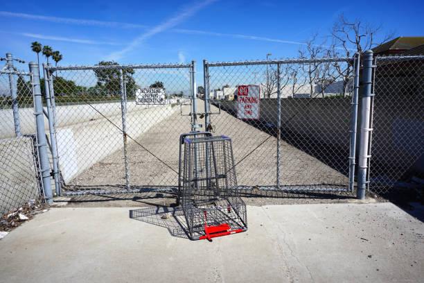 zaun und verlassene einkaufswagen - maschendrahtzaun preis stock-fotos und bilder