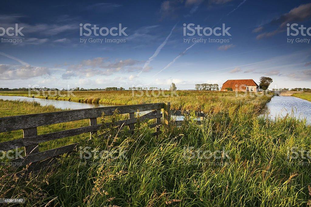 fence and farmhouse in Dutch farmland stock photo