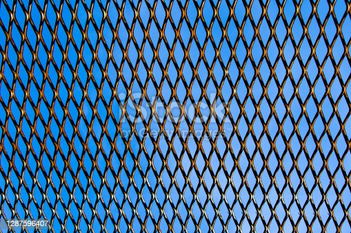 Metal fence background, real fence close-up and texture on the white sky background and texture